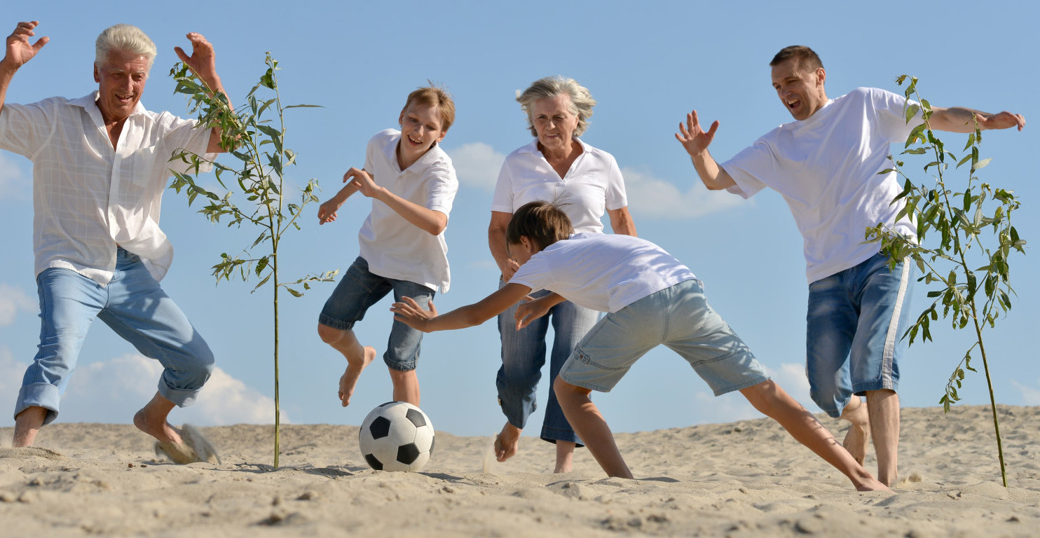 Family soccer game on beach