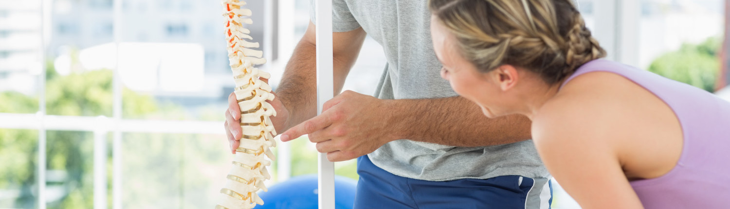 Female patient looking at chiropractic spine model
